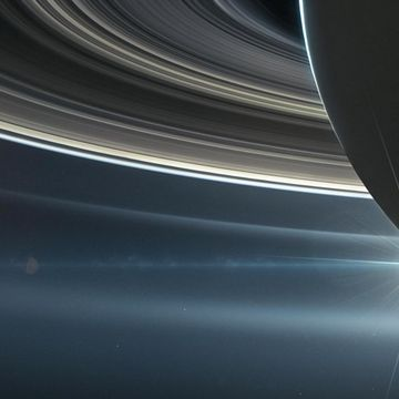 Saturn's rings paint some of its moons shades of blue and red